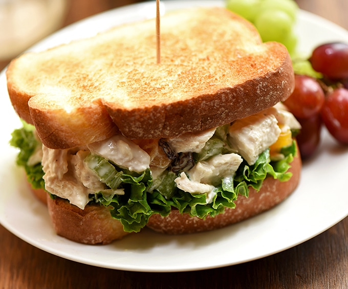 Apricot and cashew chicken salad sandwich is perfect when served on toasted bread with green leaf lettuce.