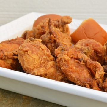 crispy buttermilk fried chicken with a side of dinner roll on a serving dish