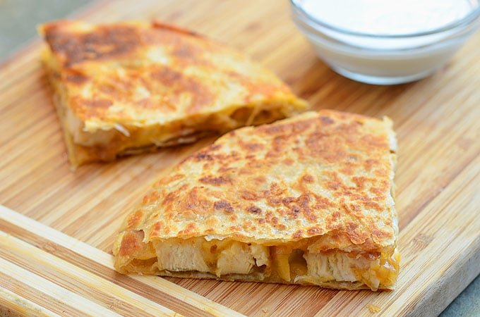 sliced chicken quesadilla with caramelized onions on a cutting board