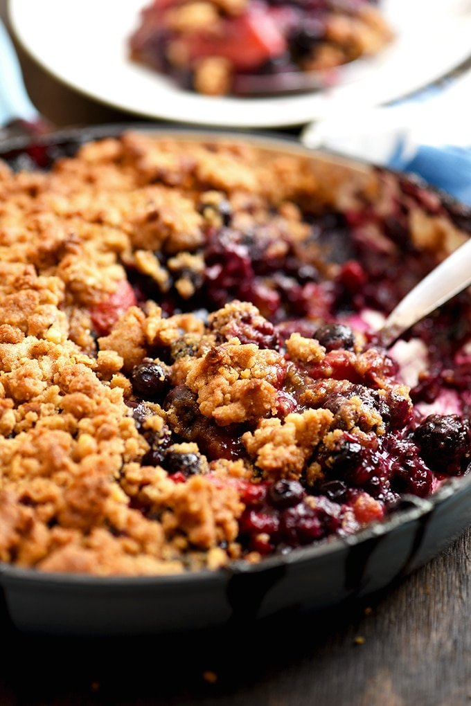 Mixed Berry Crumble in a blue skillet with spoon to serve