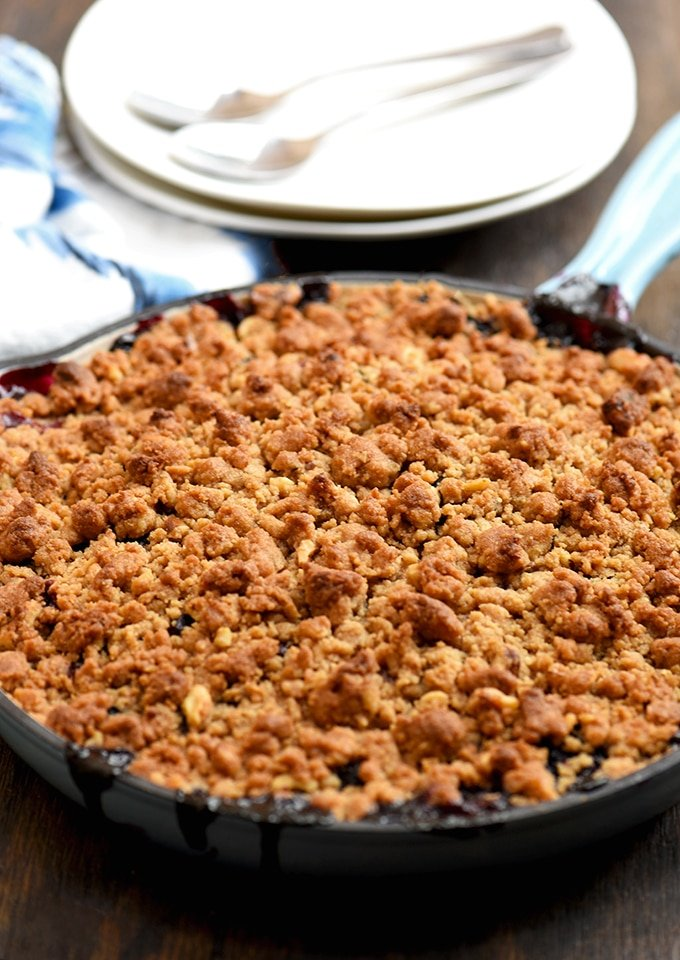 Berry Crisp with assorted berries and buttery crumble on top baked in a blue skillet