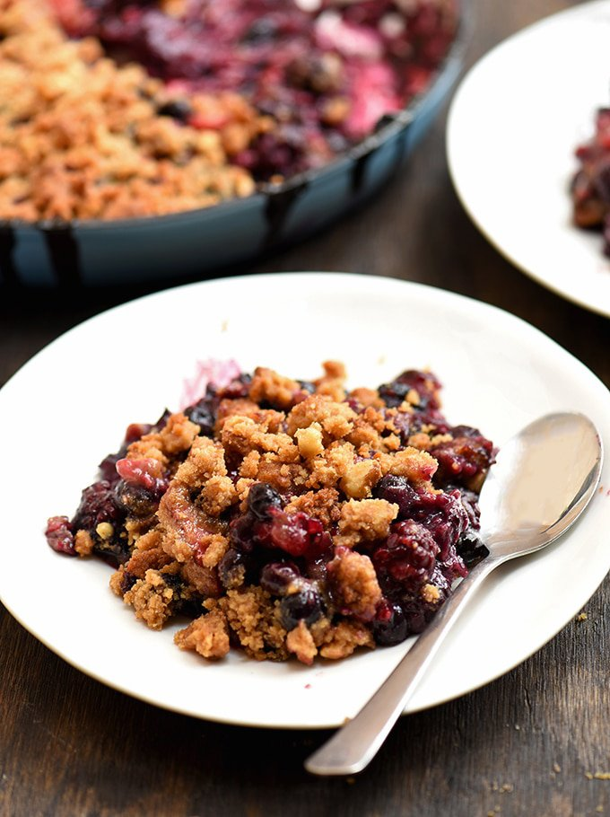 Berry crumble on a white plate with buttery crumble