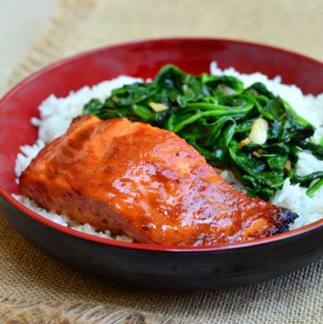 Sweet Chili Salmon with Garlic Spinach topped with sweet chili glaze and served over a bed of garlicky spinach. It makes a flavorful dinner meal and it's ready in minutes!