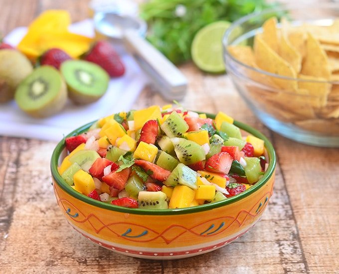 kiwi, mango and strawberry salsa in a serving bowl with a side of corn chips