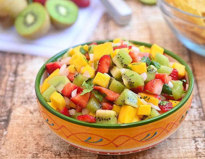 mango salsa with kiwi and strawberries in a serving bowl