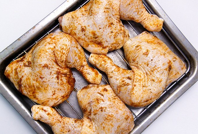 brined and seasoned chicken leg quarters on a roasting rack