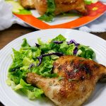 Brined Roasted Chicken on a serving plate with green salad