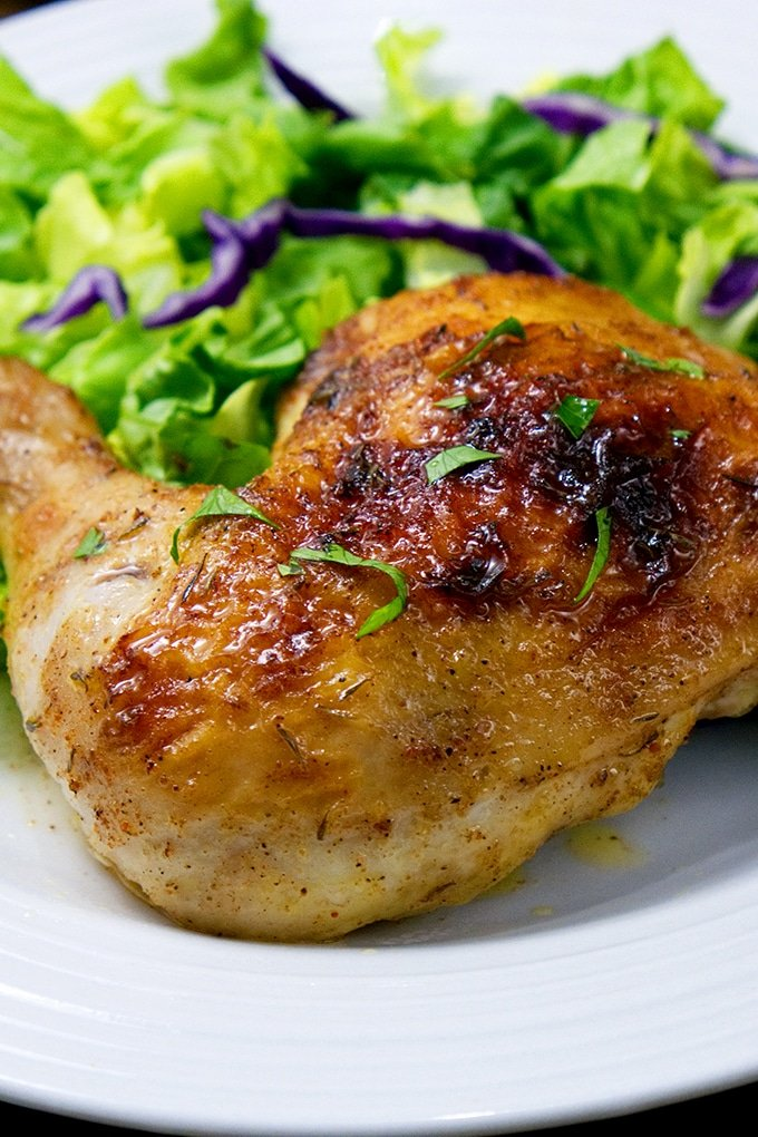 roasted chicken served on a white plate with green salad