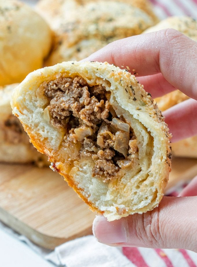 holding cut sloppy joe bread roll with hand