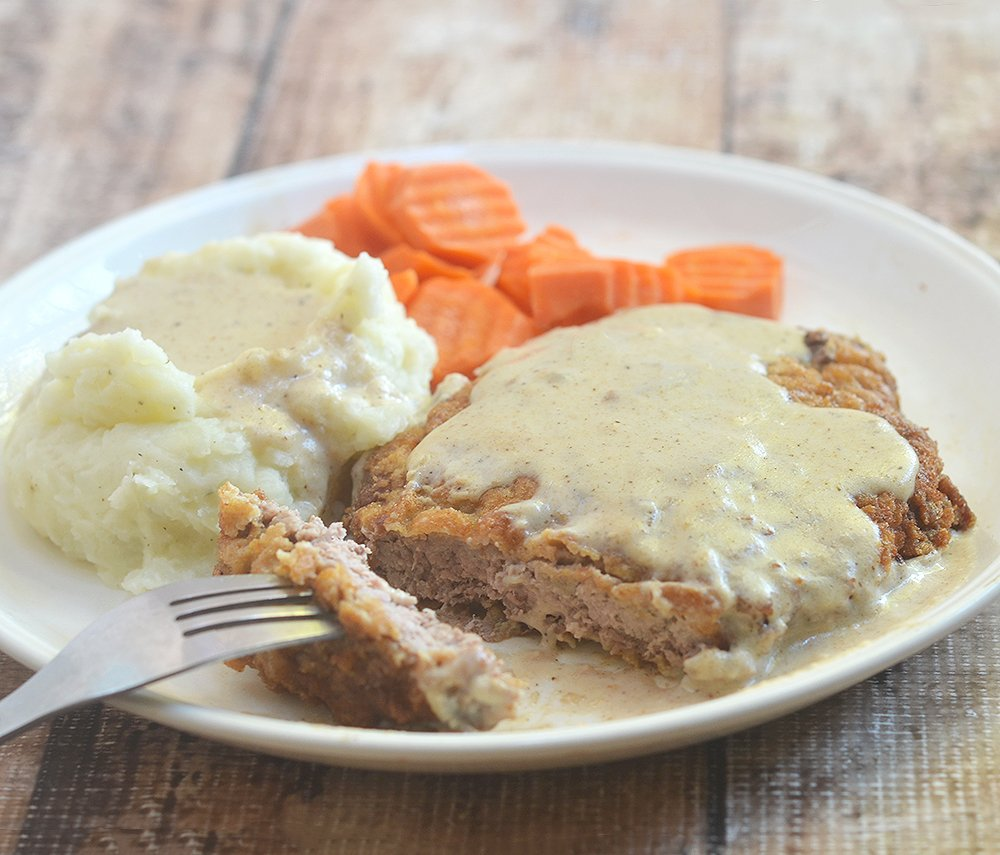 Country Fried Steak recipe made crispy yet super tender with buttermilk marinade. Serve with milk gravy for a hearty breakfast, lunch or dinner meal!
