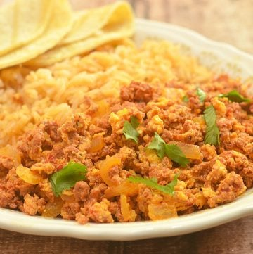 Chorizo con Huevos made with crumbled Mexican sausage and scrambled eggs. Hearty and delicious, it's perfect paired with Spanish rice and beans for breakfast as well as fillings for tacos, enchiladas or burritos.