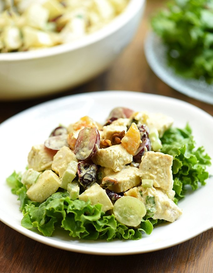 curry chicken salad with grapes, apples, dried fruit on lettuce leaves