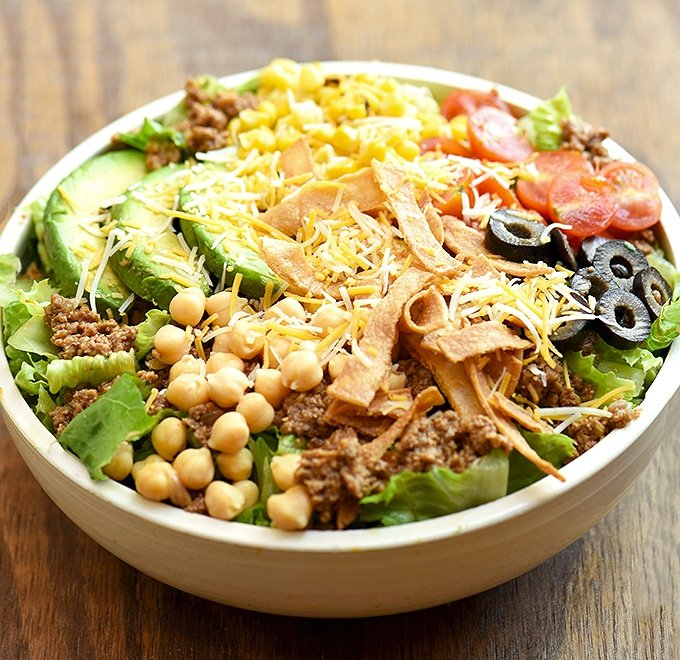 Taco Salad with lettuce, ground beef, avocados, cherry tomatoes, garbanzo beans, olives, tortilla strips and cheese in a white serving bowl