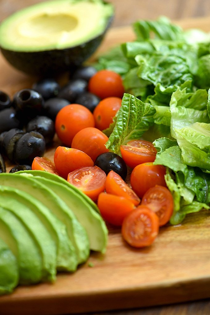 chopped romaine lettuce, cherry tomatoes, black olives, and sliced avocados on a wood cutting board