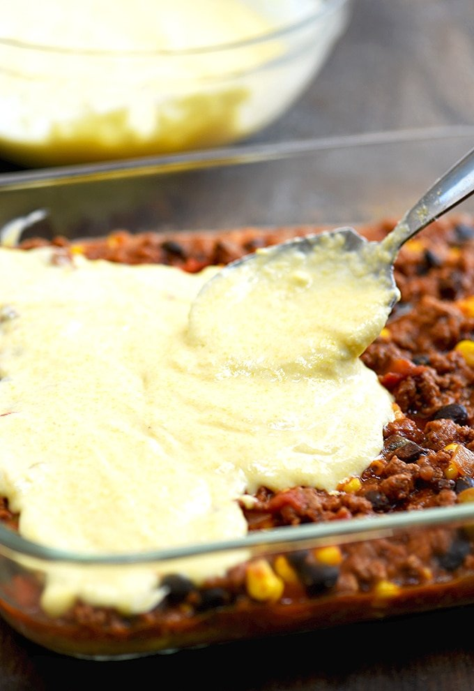 Spreading cornbread topping on tamale pie beef filling before baking up this yummy casserole.