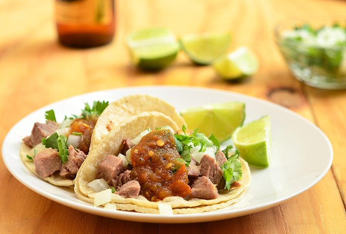 Lengua tacos with tongue, cilantro, onions, salsa roja in warm tortillas
