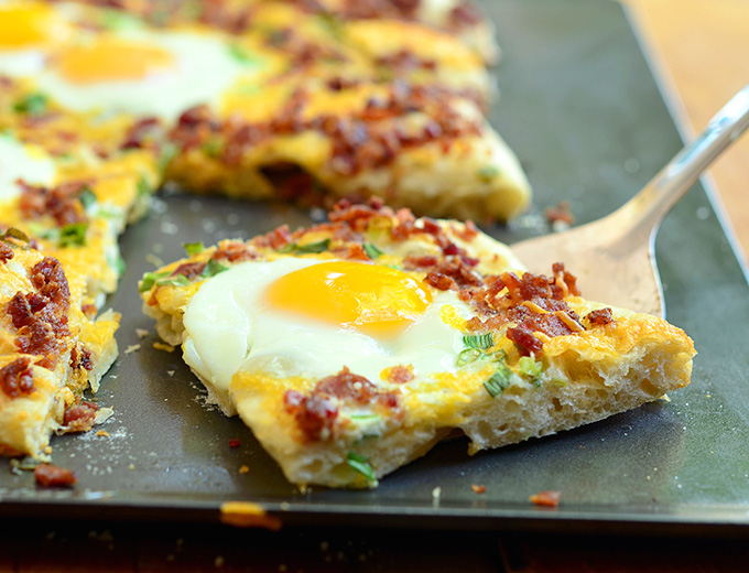 Make Breakfast Pizza with bacon, sunny side up eggs, and cheddar cheese. It's so easy to make pizza with refrigerated pizza dough!