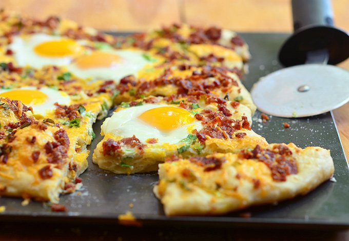 Cheesy Breakfast Pizza topped with crumbled bacon, sharp cheddar cheese, and sunny-side up eggs. Hearty and delicious, it's the best way to start your day!