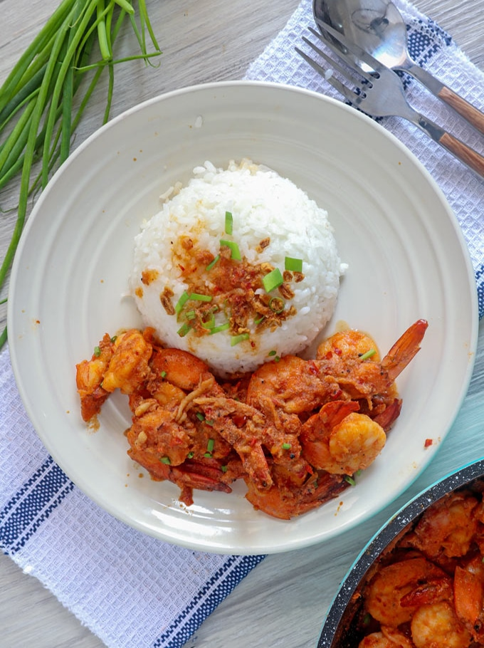 spicy shrimp in chili garlic sauce with rice on a white plate