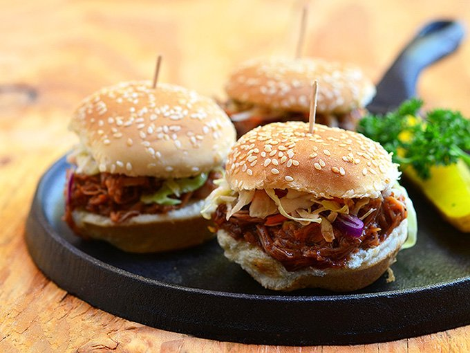 Slow Cooker Root Beer Pulled Pork Sliders made of moist slow cooker pulled pork and tangy coleslaw in slider buns. With loads of flavor and in fun size, they're perfect for tailgating!