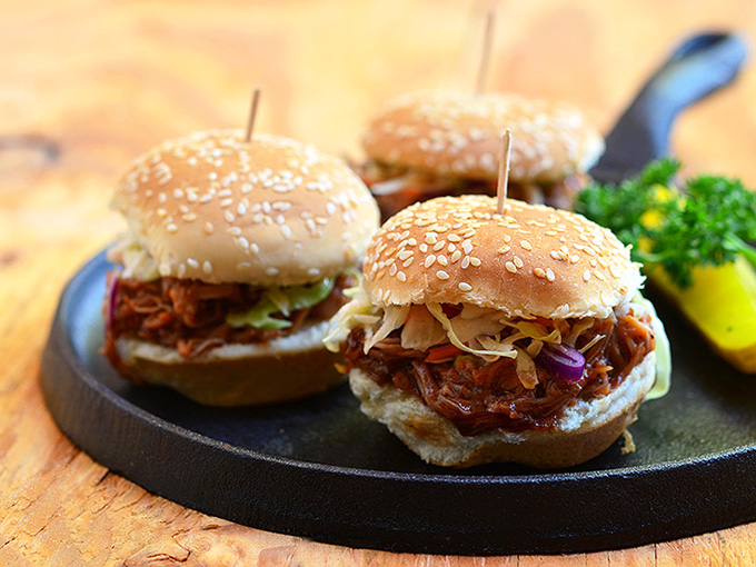 Slow Cooker Root Beer Pulled Pork Sliders made of moist slow cooker pulled pork and tangy coleslaw in slider buns. With loads of flavor and in a fun size, they're perfect for tailgating!