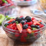 berry salsa with blueberries, blackeberries, strawberries and raspberries in a clear serving bowl with a side of tortilla chips