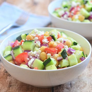 Cucumber Tomato and Feta Salad with crisp cucumbers, tomatoes, garbanzo beans, and red onions tossed in a tangy red wine vinaigrette. Chock-full of amazing texture and flavor, it's sure to be a hit with the crowd!