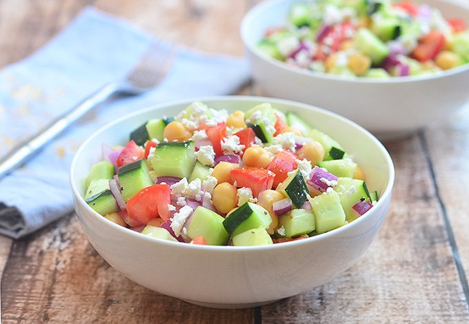 Cucumber Tomato and Feta Salad with crisp cucumbers, tomatoes, garbanzo beans, and red onions tossed in a tangy red wine vinaigrette.