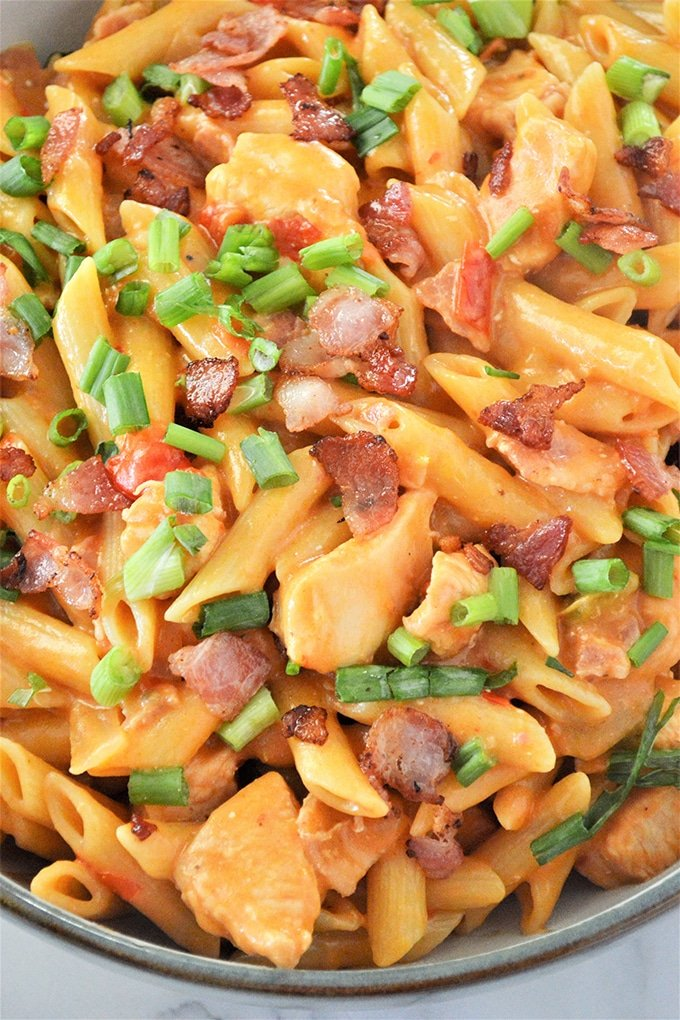 bbq chicken pasta in a bowl with green onions and bacon crumbles