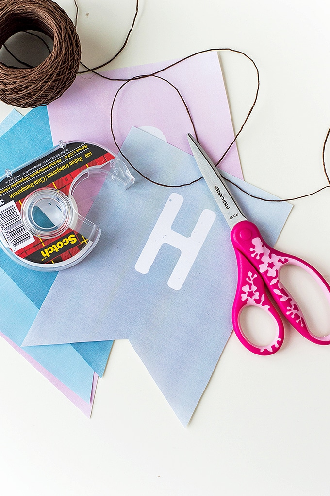 cut out Valentine's Day banner printable, kitchen twine, tape, and scissors