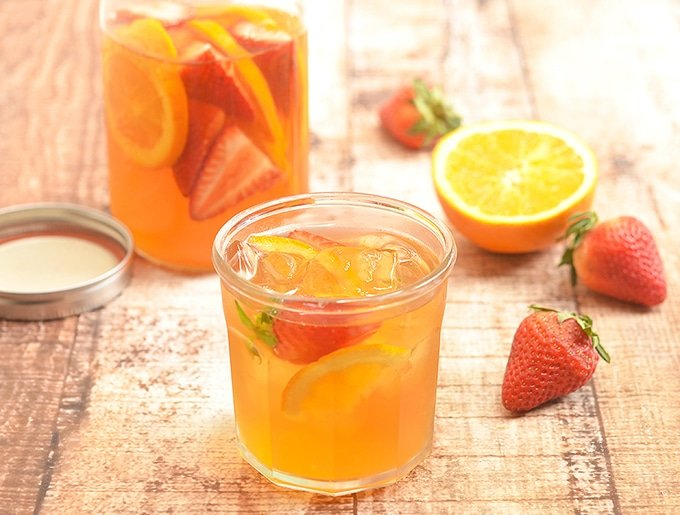 Cold brew iced tea with strawberries and oranges is a sweet and refreshing summer beverage