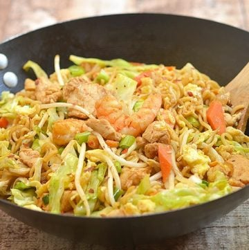 dragon noodles with chicken, shrimp and vegetables stir-fried in a wok