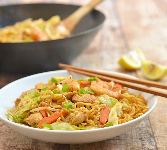 stir-fried ramen noodles with chicken, shrimp, and vegetables on a serving plate