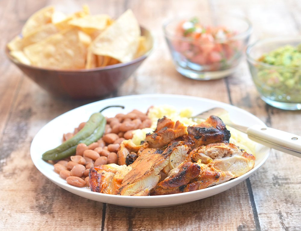 Pollo Asado marinated in citrus juices and spices is delicious fresh off the grilland leftovers are amazing in tacos, burritos or quesadillas!