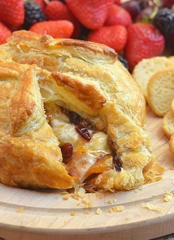 cut Brie en Croute with with fresh fruits on a wooden board