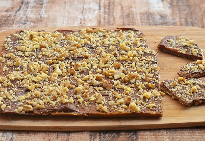 one whole slab of saltine toffee bark on a wooden board