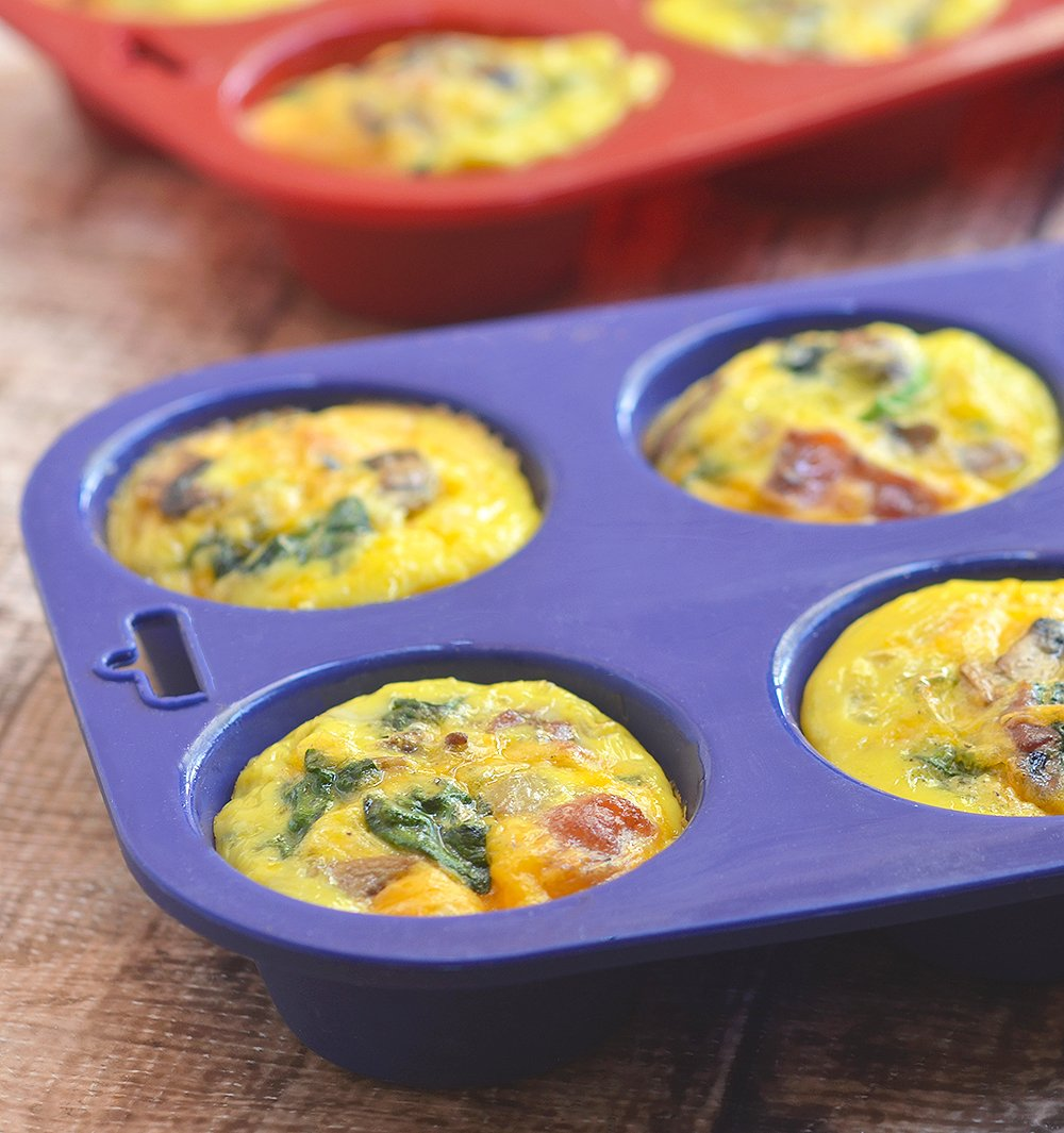 Bacon Spinach and Mushroom Egg Muffins loaded with crisp bacon, meaty mushrooms, and baby spinach. An excellent source of protein and full of healthy veggies, these portable mini frittatas are nutritious as they are delicious!