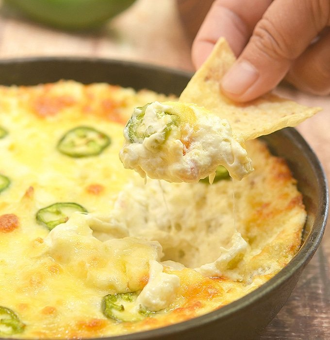 dipping corn chips in Cheesy Jalapeno Popper Dip baked in a cast iron skillet