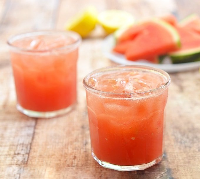 watermelon lemonade in clear glasses with watermelon and lemon slices on the side