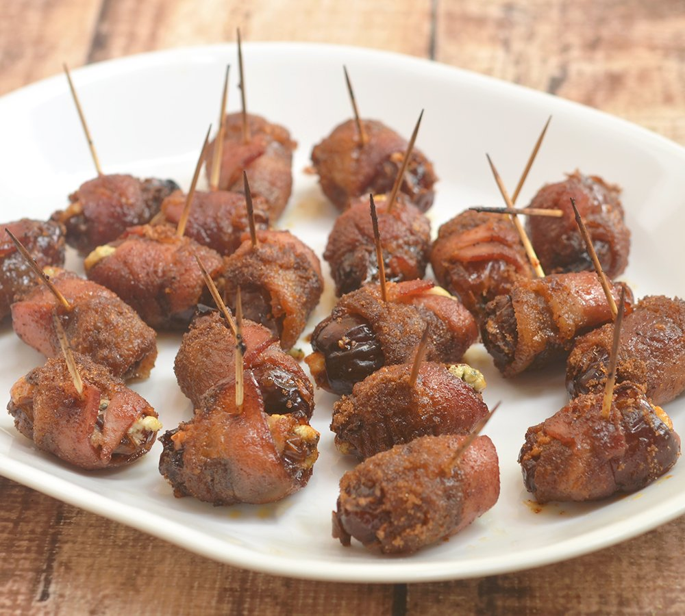 Brown Sugar Devils on Horseback made of Medjool dates stuffed with pungent blue cheese, wrapped in bacon, and baked until golden and crisp. A delicious medley of sweet and savory, these bite-sized appetizers are sure absolutely addicting!