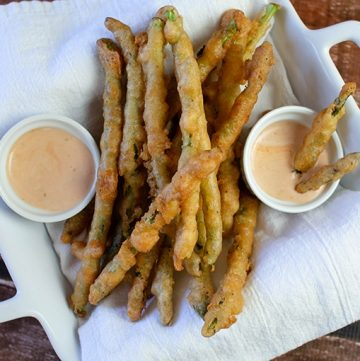 fried asparagus with beer batter in a white dish