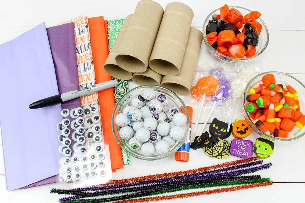 You only need simple supplies to make these Halloween party poppers, like tissue paper, candy, pipe cleaners, and paper towel cores!