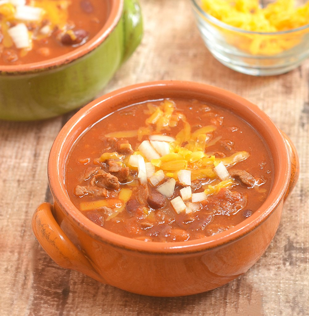 Cowboy Steak Chili with diced beef and tender beans in a smoky, chili-spiced tomato gravy is the ultimate chilly day food. Serve with various fixings and toppings!
