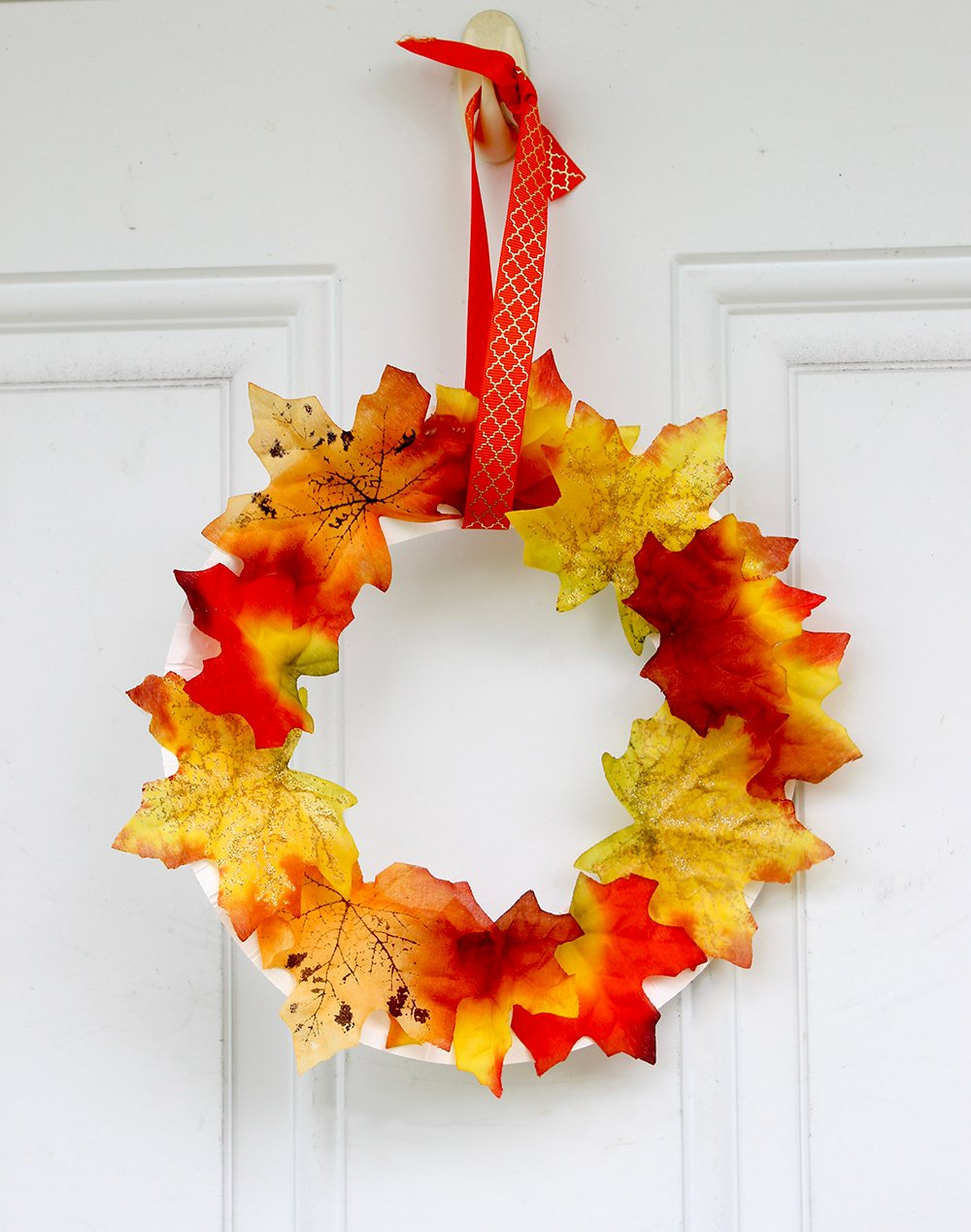 A simple Fall ribbon is the final touch to make this Fall wreath door decor ready