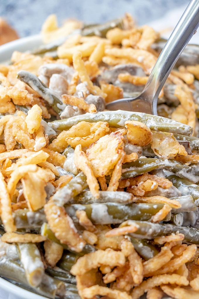 stirring green beans with crispy fried onions, mushrooms, and cream sauce with a fork