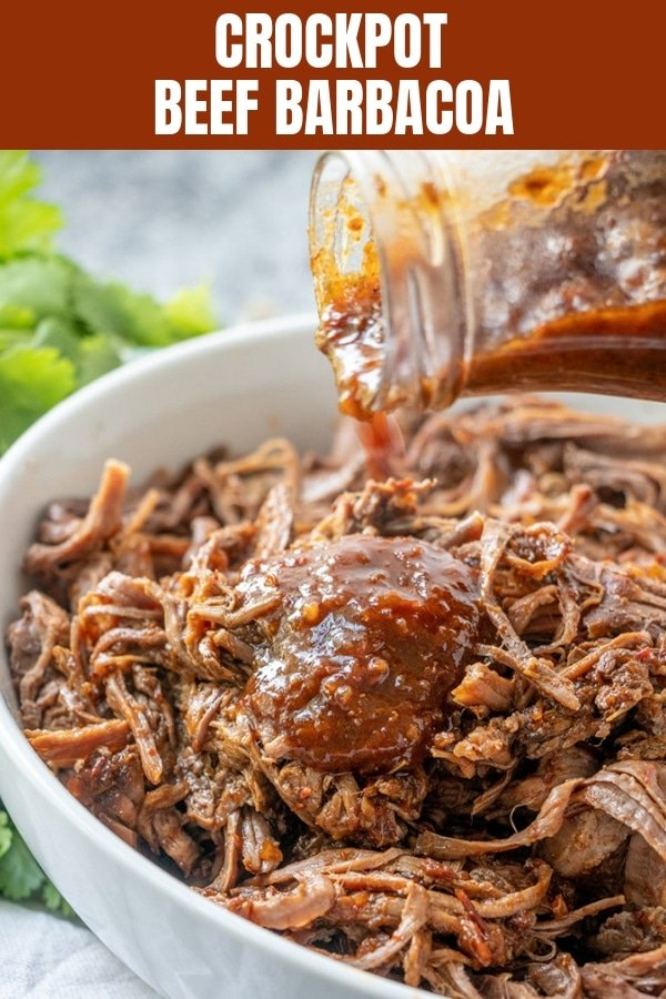 pouring sauce onto Barbacoa Beef in a white bowl