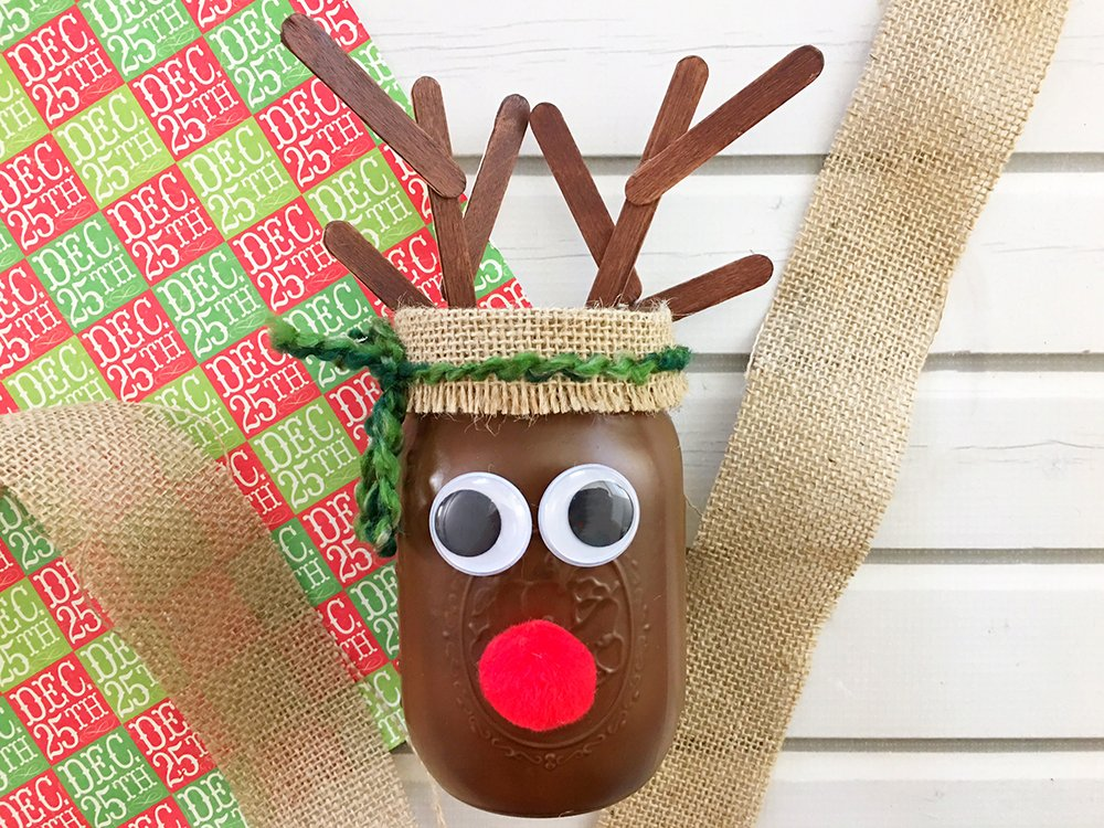 DIY Christmas Reindeer Mason Jar is perfect for holiday gift giving and home decorating. It's a fun and easy Christmas craft activity for the whole family!-tie green yarn around burlap into a bow