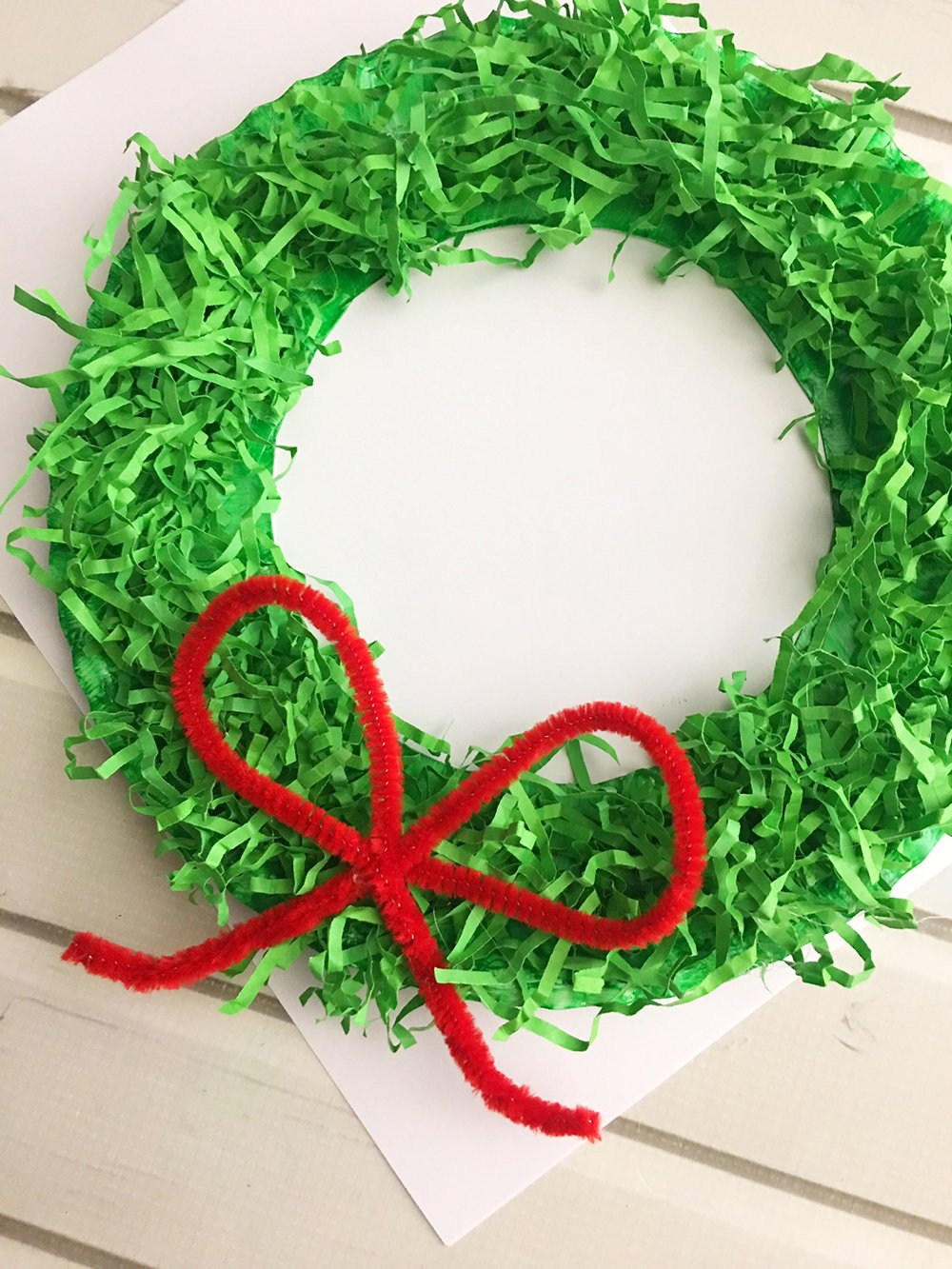 DIY Paper Christmas Wreath made with paper plate and shredded crinkle paper adds a festive touch to your holiday decor-Glue the pipe cleaner bow to the bottom center of the paper wreath.