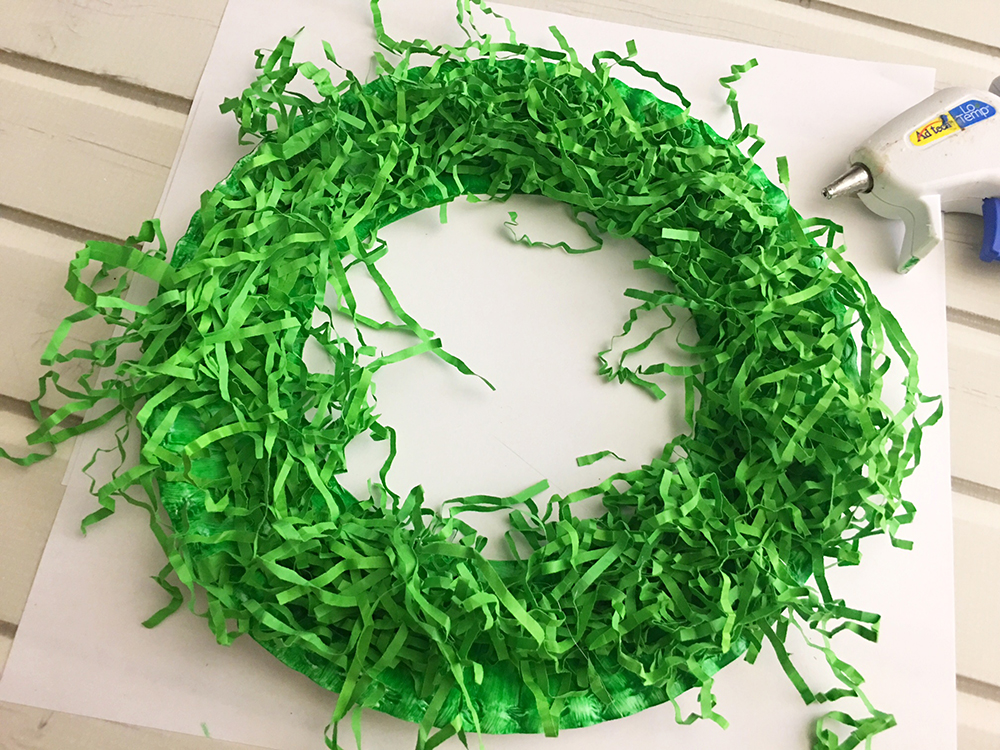 DIY Paper Christmas Wreath made with paper plate and shredded crinkle paper adds a festive touch to your holiday decor-glue shredded crinkle paper to paper plate circle to cover