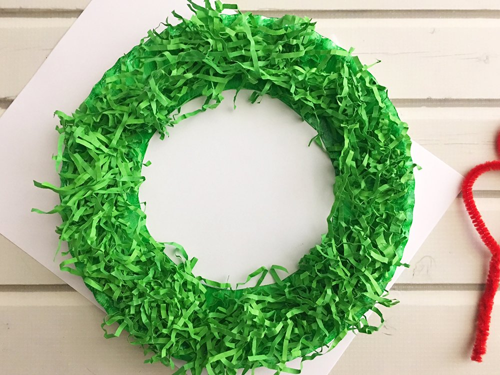 DIY Paper Christmas Wreath made with paper plate and shredded crinkle paper adds a festive touch to your holiday decor-trim off excess crinkle paper haging on the inside and outside of paper wreath